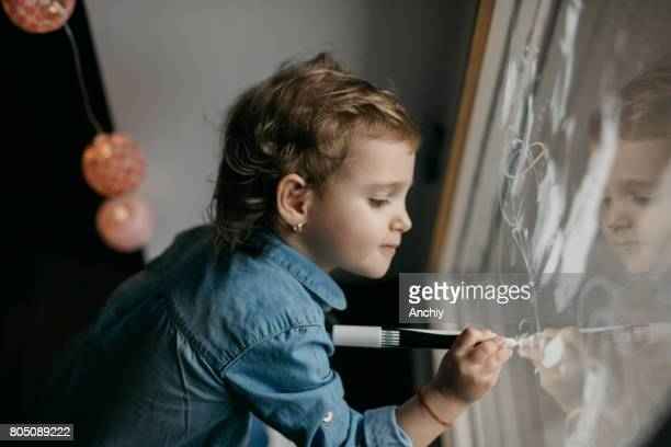Adorable little girl drawing various objects on the window