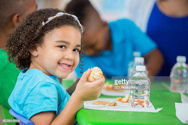 Adorable little girl eating an orange during daycare snack time