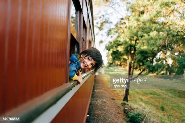 Adorable little girl enjoying train ride through countryside