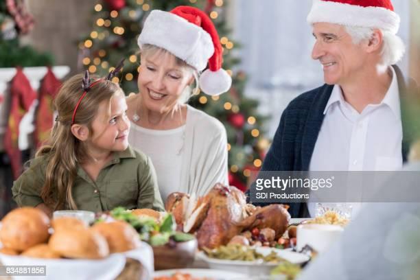 Schattig meisje geniet van grootvader grap op kerstdiner