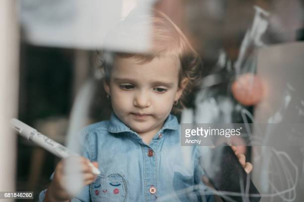 Adorable little girl is drawing on the window with white marker