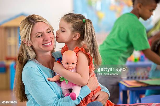 Adorable little girl kisses her mother goodbye at daycare center