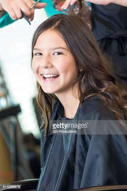 Adorable petite fille souriant dans un salon de coiffure