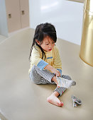 Adorable little girl trying to put a socks.