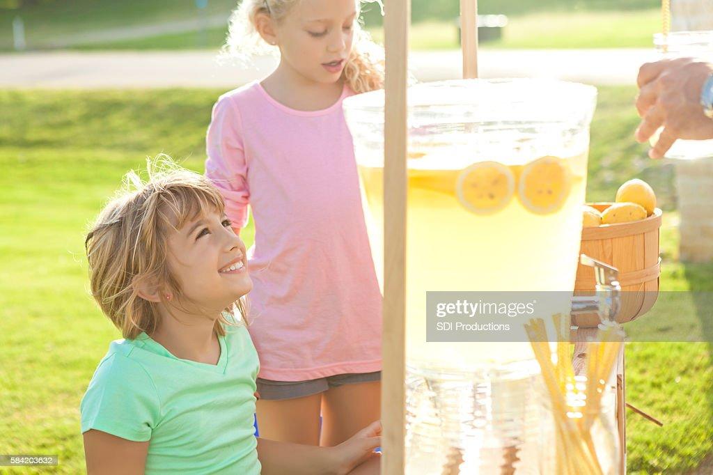 Adorable little girls selling lemonade on a hot summer day
