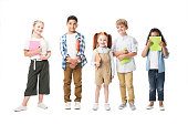 adorable multiethnic children holding textbooks and smiling at camera isolated on white