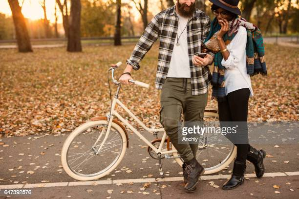 Adorable multi-ethnic couple posing in front of the bike in the park at autumn