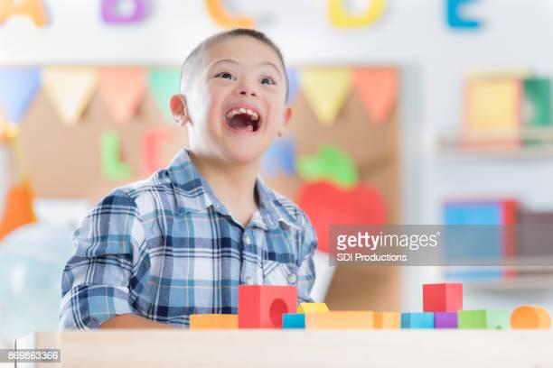 Adorable preschool age boy in daycare classroom