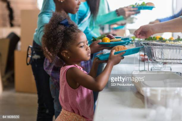 Adorable preschool age girl receives meal in soup kitchen