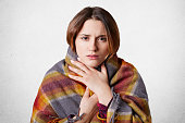 Adorable pretty woman feels frozen, covered in warm plaid, isolated over white concrete background. Female model has cold, tries to warm herself under wool blanket, enjoys domestic atmosphere