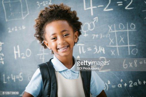 Adorable private school kindergarten girl smiling in front of blackboard