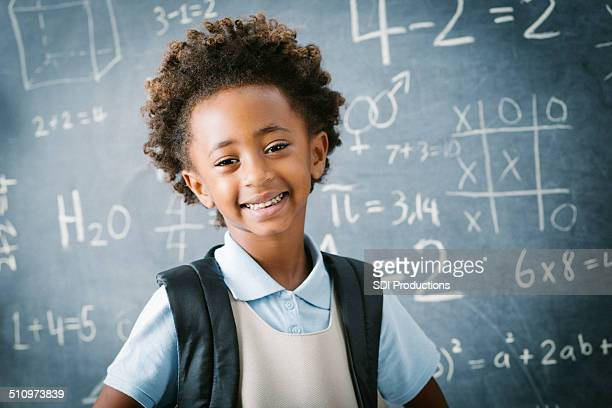 Adorable private school kindergarten girl smiling in front of blackboard