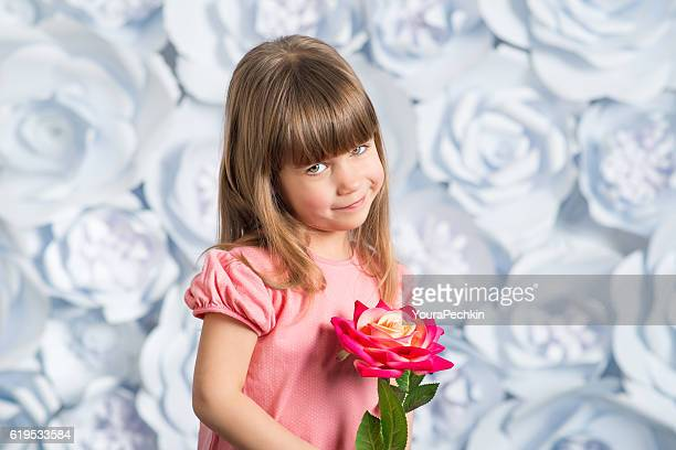 Adorable smiling little girl with artificial flower