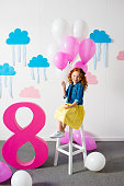 adorable smiling redhead girl sitting on stool with balloons at birthday party