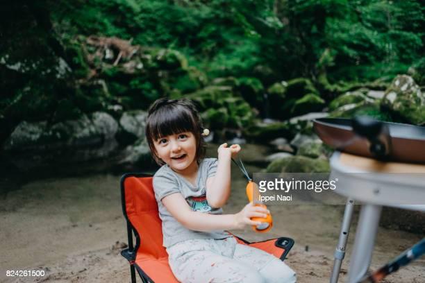 Adorable toddler girl enjoying camping in nature