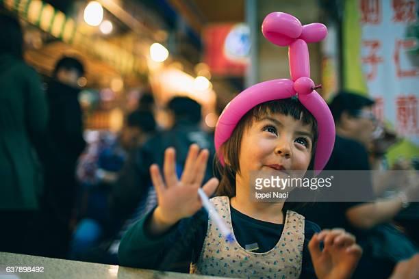 Adorable toddler girl having fun at night market, Taiwan