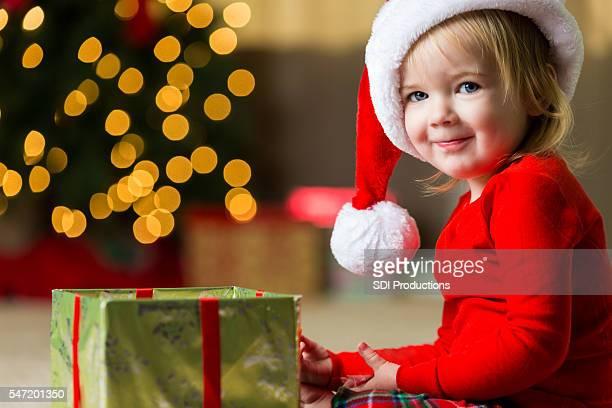 Adorable toddler girl opening Christmas gift