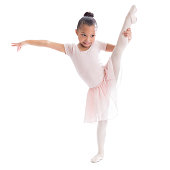 Cute preschool age African American female ballerina stretches out her leg in ballet pose.