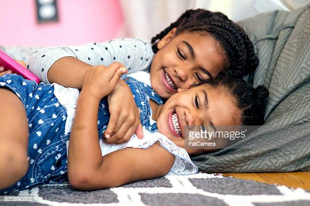 Adorable young African American twins hugging each other