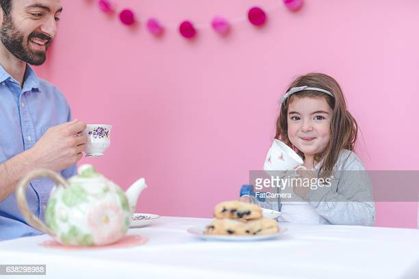 Adorable young girl having a tea party with her father