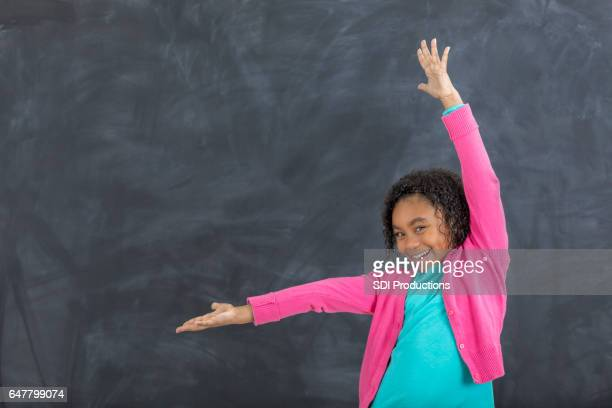 Adorable young girl in front of chalkboard in classroom