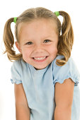 Beautiful smile and pigtails on the effervescent face of a 3 year old girl. She has her shoulders shrugged upward for this headshot.