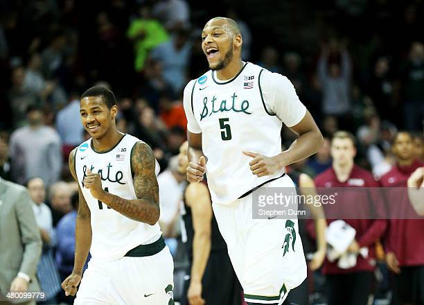 Adreian Payne and Keith Appling of the Michigan State Spartans celebrate their 80 to 73 win over the Harvard Crimson during the Third Round of the...