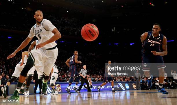 Adreian Payne of the Michigan State Spartans and Phillip Nolan of the Connecticut Huskies chase after a loose ball during the East Regional Final of...