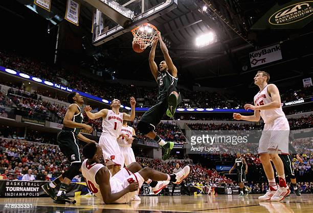 Adreian Payne of the Michigan State Spartans dunks the ball over Nigel Hayes of the Wisconsin Badgers who falls to the floor during the first half of...
