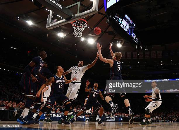 Adreian Payne of the Michigan State Spartans fights for the ball against Niels Giffey Amida Brimah and Shabazz Napier of the Connecticut Huskies...