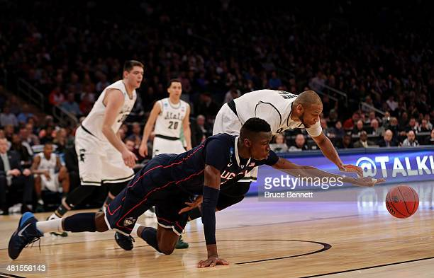 Adreian Payne of the Michigan State Spartans fights for the loose ball against Amida Brimah of the Connecticut Huskies in the first half of the East...
