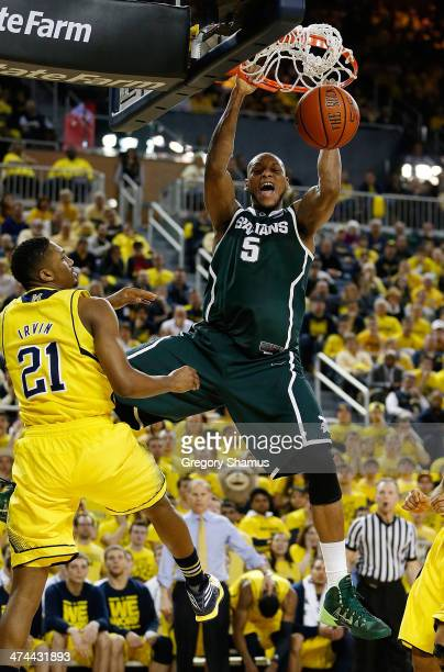 Adreian Payne of the Michigan State Spartans gets in for a first half dunk next to Zak Irvin of the Michigan Wolverines at Crisler Center on February...
