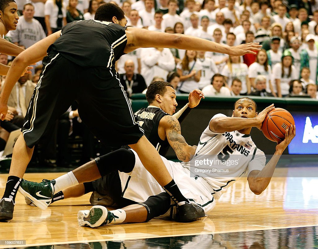 Adreian Payne #5 of the Michigan State Spartans looks to take a shot while sitting on the floor between A.J. Hammons #20 and Anthony Johnson #1 of the Purdue Boilermakers at the Jack T. Breslin Student Events Center on January 5, 2013 in East Lansing, Michigan. Michigan State won the game 84-61.