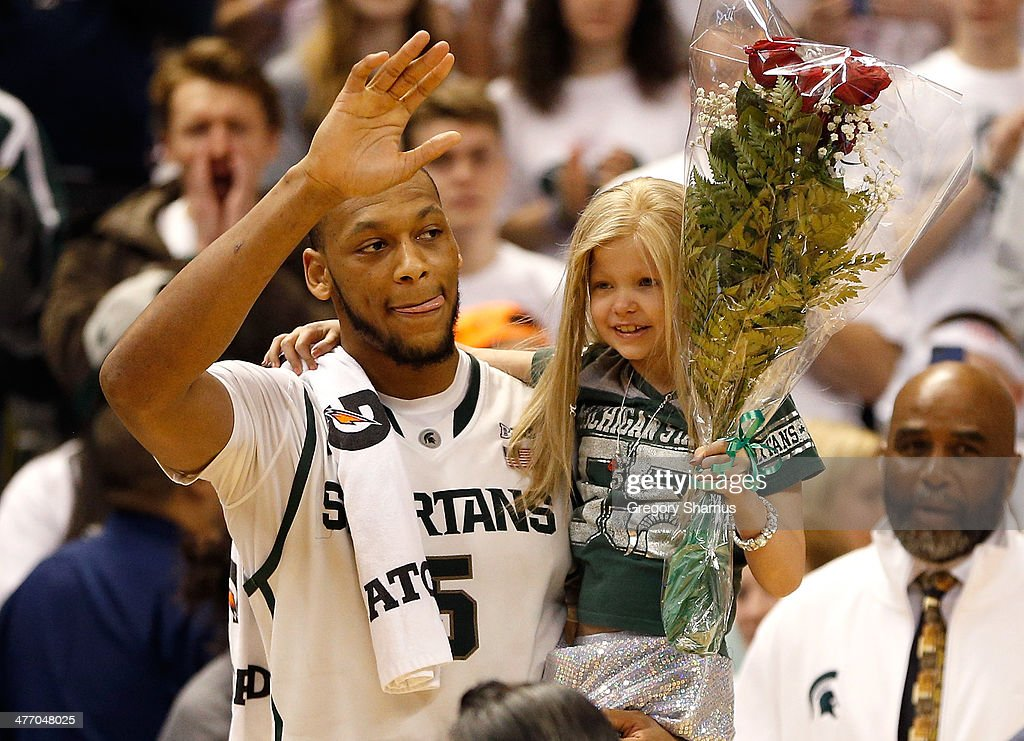 <a gi-track='captionPersonalityLinkClicked' href=/galleries/search?phrase=Adreian+Payne&family=editorial&specificpeople=7367769 ng-click='$event.stopPropagation()'>Adreian Payne</a> #5 of the Michigan State Spartans walks on the floor for Senior night with Lacey Holsworth, a 8-year-old from St. Johns Michigan who is battling cancer, after defeating the Iowa Hawkeyes 86-76 at the Jack T. Breslin Student Events Center on February 6, 2014 in East Lansing, Michigan.