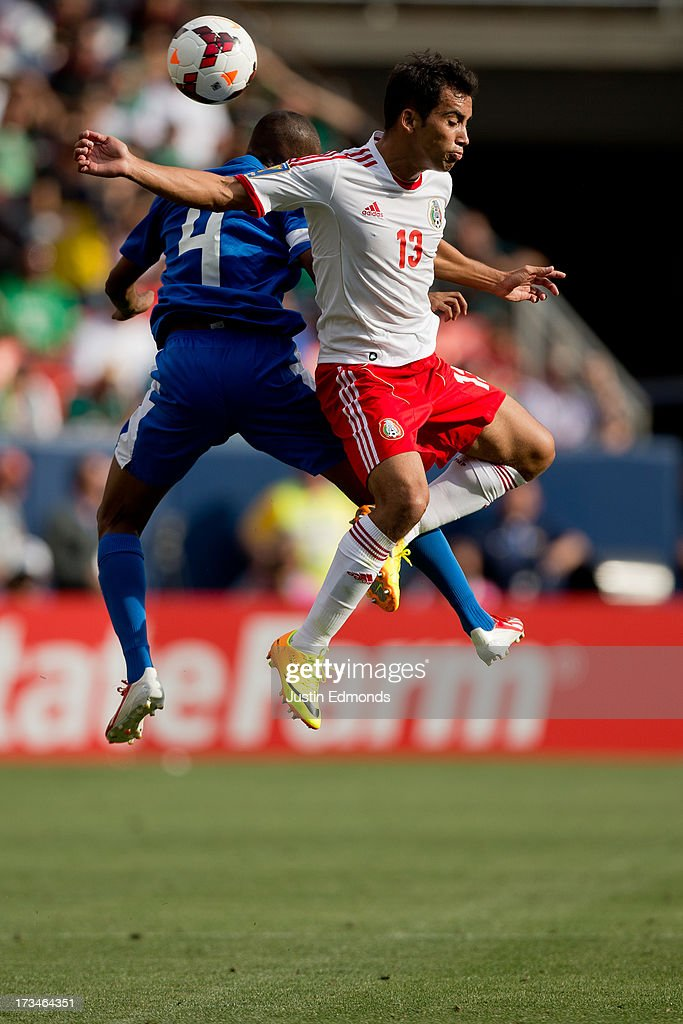 Adrian Aldrete #13 of Mexico battles for a ball in the air with Daniel Herelle #4 of Martinique during the second half of a CONCACAF Gold Cup match at Sports Authority Field at Mile High on July 14, 2013 in Denver, Colorado. Mexico defeated Martinique 3-1.