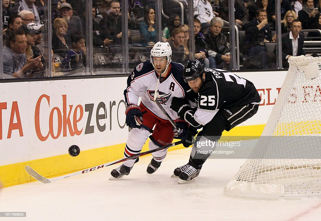 Adrian Aucoin #33 of the Columbus Blue Jackets and Dustin Penner #25 of the Los Angeles Kings skate after the puck behind the Blue Jackets net during the NHL game at Staples Center on February 15, 2013 in Los Angeles, California. The Kings defeated the Blue Jackets 2-1.