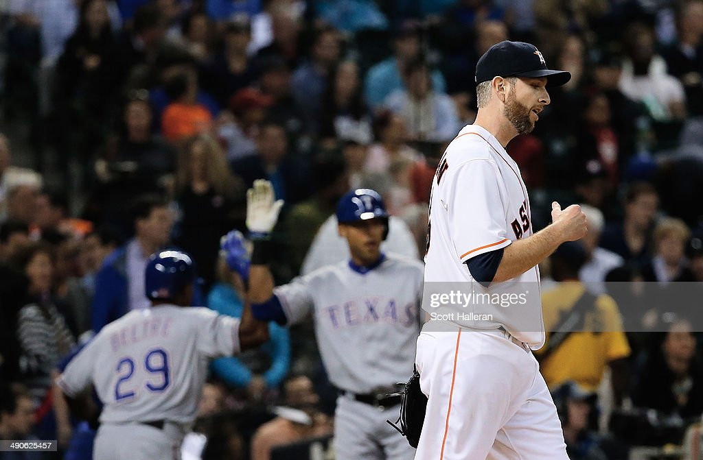 Adrian Beltre #29 and Alex Rios #51 of the Texas Rangers celebrate after Beltre scored a run in the fifth inning as Scott Feldman #46 of the Houston Astros looks on during their game at Minute Maid Park on May 14, 2014 in Houston, Texas.