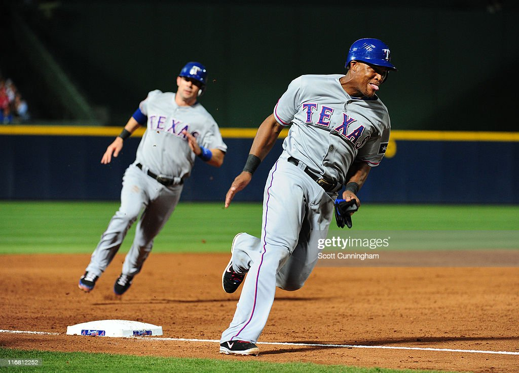 Adrian Beltre and Michael Young of the Texas Rangers round 3rd base to score against the Atlanta Braves at Turner Field on June 17 2011 in Atlanta...