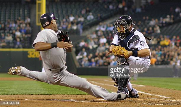 Adrian Beltre of the Boston Red Sox slides into home plate against catcher Adam Moore of the Seattle Mariners attempting to score on a single by...