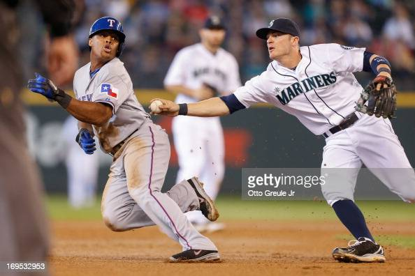 Adrian Beltre of the Texas Rangers attempts to elude the tag of shortstop Brendan Ryan of the Seattle Mariners in the seventh inning at Safeco Field...