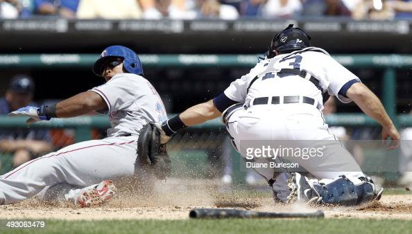 Adrian Beltre of the Texas Rangers beats the tag from catcher Alex Avila of the Detroit Tigers to score in the third inning at Comerica Park on May...
