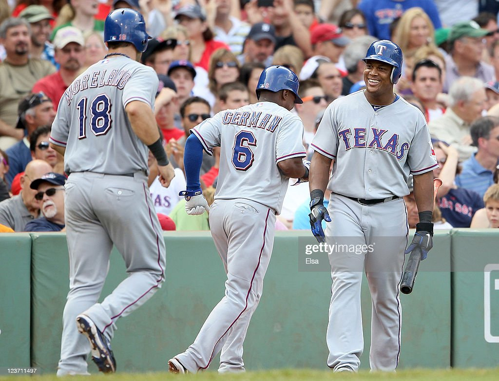 <a gi-track='captionPersonalityLinkClicked' href=/galleries/search?phrase=Adrian+Beltre&family=editorial&specificpeople=202631 ng-click='$event.stopPropagation()'>Adrian Beltre</a> #29 of the Texas Rangers congratulates teammates <a gi-track='captionPersonalityLinkClicked' href=/galleries/search?phrase=Esteban+German&family=editorial&specificpeople=225177 ng-click='$event.stopPropagation()'>Esteban German</a> #6 and <a gi-track='captionPersonalityLinkClicked' href=/galleries/search?phrase=Mitch+Moreland&family=editorial&specificpeople=6824046 ng-click='$event.stopPropagation()'>Mitch Moreland</a> #18 after they scored on a triple hit by Josh Hamilton in the sixth inning against the Boston Red Sox on September 4, 2011 at Fenway Park in Boston, Massachusetts.