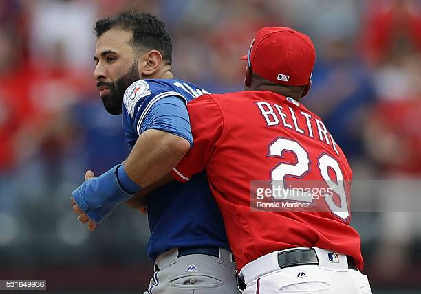 Adrian Beltre of the Texas Rangers holds Jose Bautista of the Toronto Blue Jays after being punched by Rougned Odor in the eighth inning at Globe...