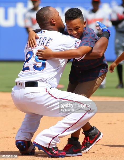 Adrian Beltre of the Texas Rangers hugs his son Adrian Jr after hitting his 3000th MLB career hits in the fourth inning against the Baltimore Orioles...