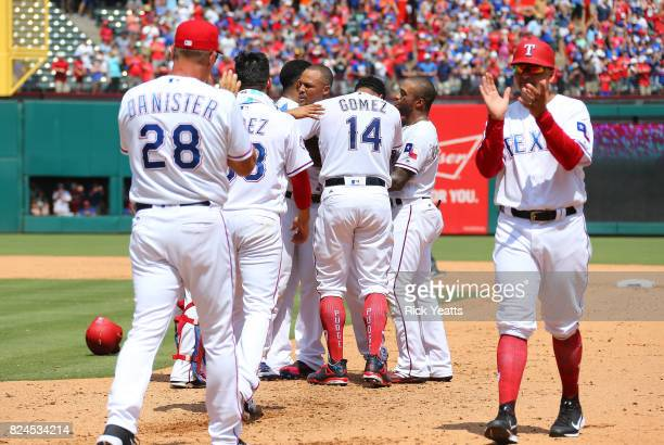 Adrian Beltre of the Texas Rangers is congratulated by Carlos Gomez and other teammates after hitting his 3000th MLB career hit in the fourth inning...