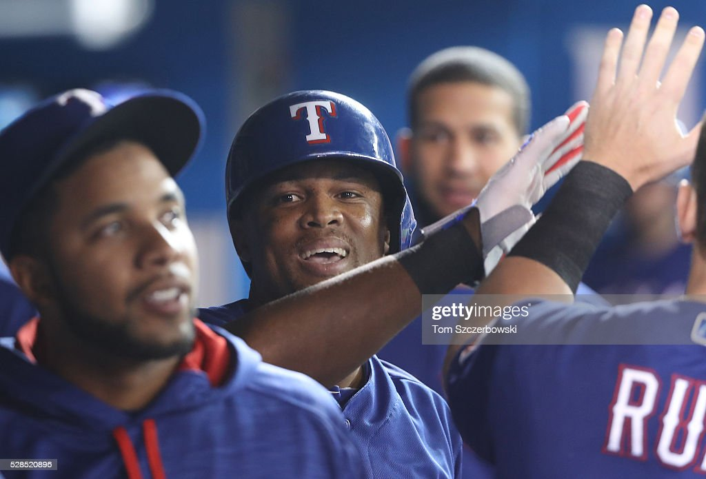 Adrian Beltre #29 of the Texas Rangers is congratulated by teammates in the dugout after scoring a run in the first inning during MLB game action against the Toronto Blue Jays on May 5, 2016 at Rogers Centre in Toronto, Ontario, Canada.