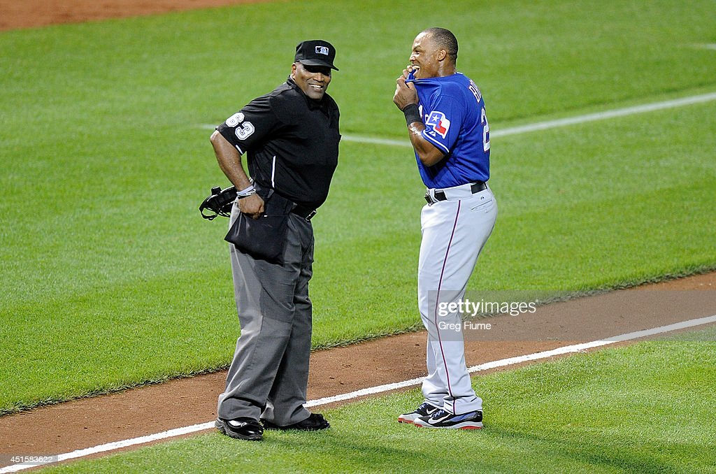 Adrian Beltre of the Texas Rangers talks with home plate umpire Laz Diaz between the sixth and seventh inning of the game against the Baltimore...