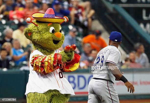 Adrian Beltre of the Texas Rangers trots out to the field past the dancing Houston Astros mascot Orbit during the first inning of their game at...