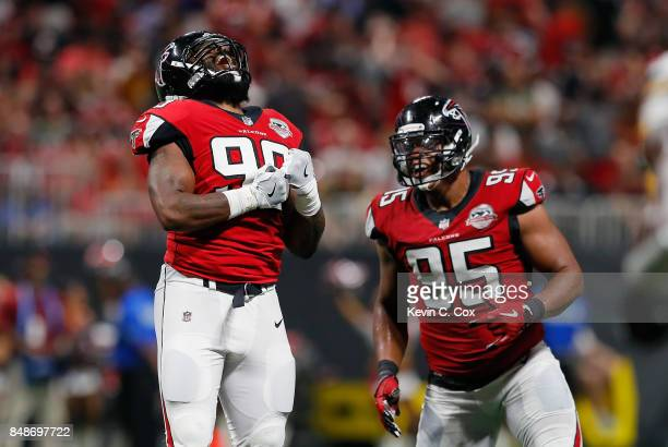 Adrian Clayborn celebrates with Jack Crawford of the Atlanta Falcons after sacking Aaron Rodgers of the Green Bay Packers during the second half at...