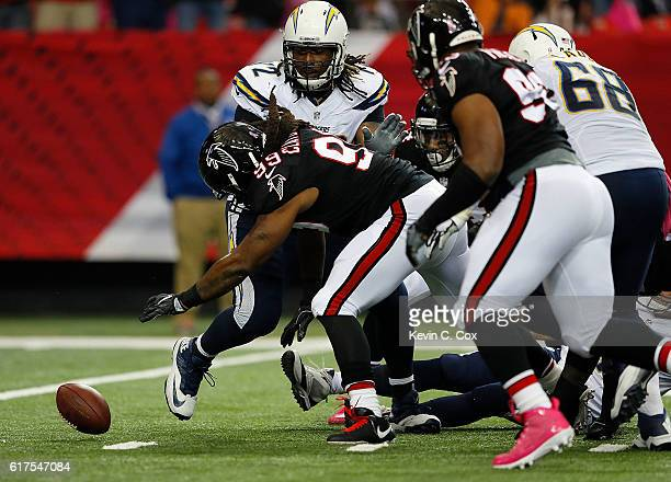 Adrian Clayborn of the Atlanta Falcons picks up a fumble on the way to scoring a touchdown against Joe Barksdale of the San Diego Chargers at Georgia...